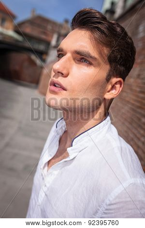 Close up picture of a handsome young casual man looking away from the camera.