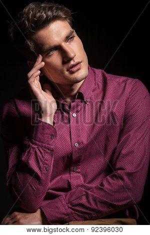 Young fashion man thinking while holding his hand to his head, looking away from the camera.