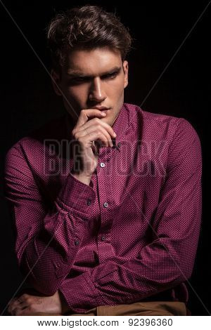 Thoughtful man holding one hand to his lip while looking away from the camera.