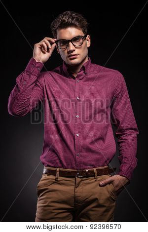Young fashion man holding his hand in pocket while fixing his glasses.
