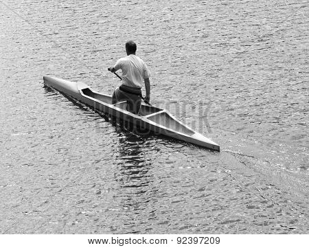 Young man canoeing in the lake at sunset. Classical black and white photography of high contrast scene.