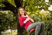 foto of seesaw  - Happy girl swinging on seesaw hanging from cherry tree behind family house - JPG