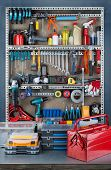 stock photo of garage  - Garage tool rack with various tools and repair supplies on board and shelves - JPG