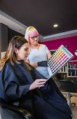 foto of hair dye  - Beautiful young woman looking with hairdresser a hair dye palette to change her hair color - JPG