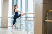 image of stretch  - in the hall girl doing stretching near Barre - JPG