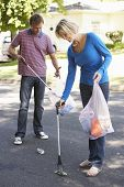 stock photo of pick up  - Couple Picking Up Litter In Suburban Street - JPG