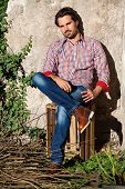 stock photo of wooden crate  - Smiling male model sitting on wooden crate with legs crossed - JPG