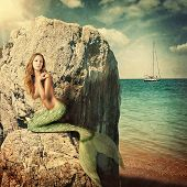 foto of mermaid  - Sexy beautiful woman mermaid with long tail sitting on a rock about sea - JPG