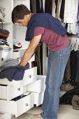 stock photo of wardrobe  - Teenage Boy Choosing Clothes From Wardrobe In Bedroom - JPG