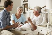 image of visitation  - Doctor On Home Visit Discussing Health Of Senior Male Patient With Wife - JPG