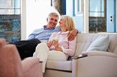 foto of hot couple  - Mature Couple At Home Relaxing In Lounge With Hot Drink - JPG