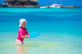 picture of frisbee  - Little girl playing frisbee on a tropical white beach - JPG