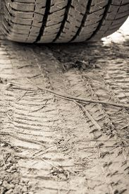 picture of track field  - Closeup texture wheel with tyre tracks in the ground in sunlight. Wheel tracks on dirt. Focus on tire track ** Note: Shallow depth of field - JPG