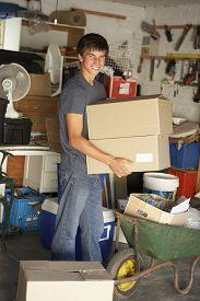 stock photo of yard sale  - Teenage Boy Clearing Garage For Yard Sale - JPG