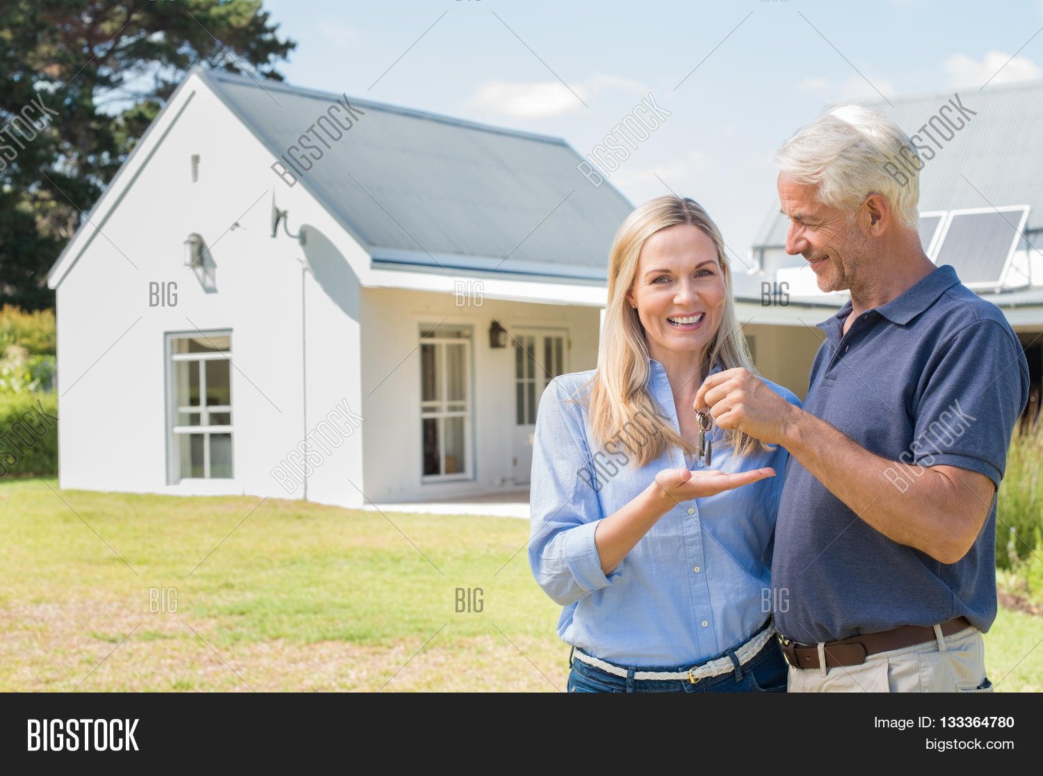Cheerful Senior Couple Standing Outside Their New House