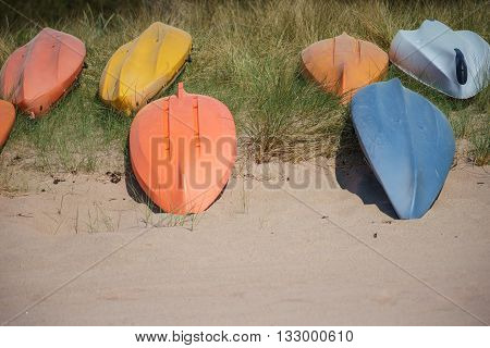 Upside down colorful kayak or canoe boats lays on sandy beach selective focus