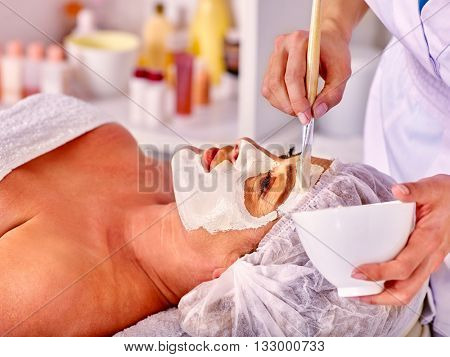Woman middle-aged take facial and neck clay mask in spa salon. Two female people. Spa procedure for middle-aged woman.