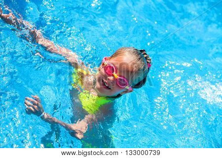 Portrait of child girl on water in swimming pool . Children's healthy lifestyle into blue water. Summer swimming holiday. Top view. Outdoor.