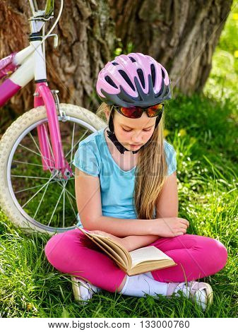 Bikes cycling girl. Girl rides bicycle. Girl in cycling sitting on green grass near bicycle and read book on rest near bicycle. Cycling is good for health.