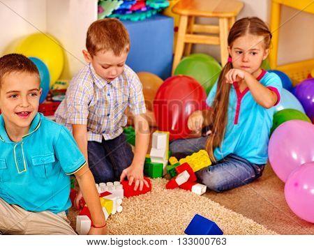 Group children game blocks on floor in kindergarten . Top view. Indoor blocks game on floor.