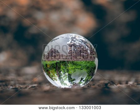 Globe on dry land. In the bowl of green trees, grass. Glass - a material, concepts and themes, concepts, environment, nature, ecology, drought