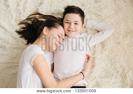 Brother and sister hugging and smiling lying on the floor