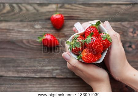Woman holds a cup full of strawberries in hands. Mug shaped as a heart symbol of love. Fresh juicy strawberry on rustic wooden background. Top view place for text.