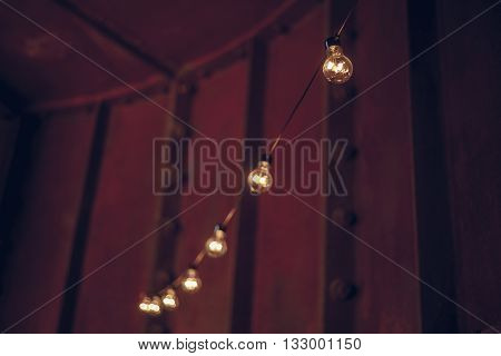 String wired bulbs hanging inside dark room festive illumination holiday concept
