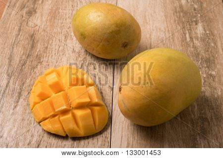 Mango slice cut to cubes with fresh mango on wooden table
