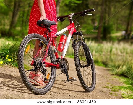 Bikes cycling girl. Body part of girl wearing red polka dots dress rides bicycle into park. Girl in ecotourism. Cycling is good for health. Cyclist is unrecognizable.