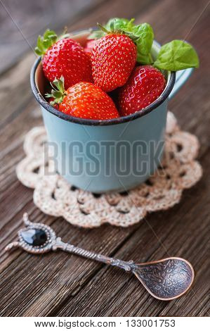 Fresh juicy strawberries in old rusty mug. Rustic wooden background with croshet napkin and vintage spoon.