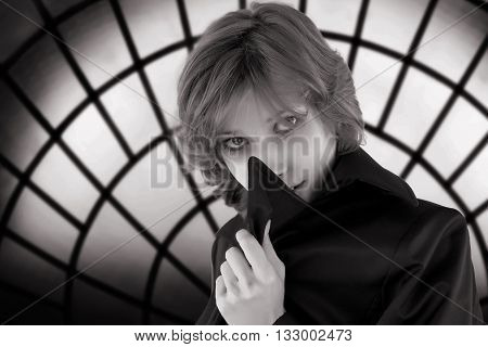 Black and white toned portrait of mysterious woman against sinister defocused stained-glass