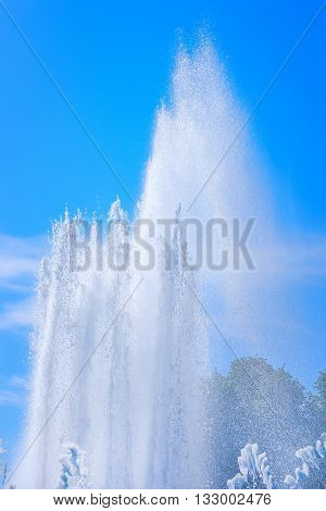 Fountain jet and water spray at sunny day against blue sky and distant threes