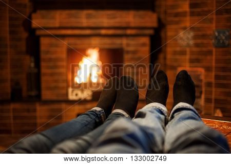 two pairs legs on the background of burning fireplace.