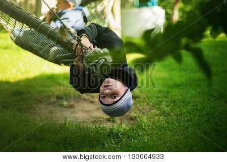 kid hanging hammock upside down backyard background selective focus