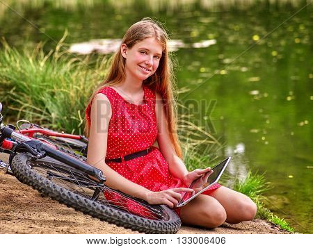Bikes cycling girl. Girl wearing red polka dots dress recreation near bicycle into park. Child watch tablet pc. Girl in ecotourism.