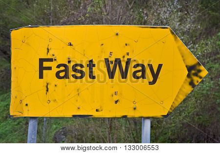 Text Fast Way written on a yellor road sign