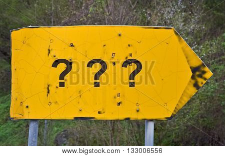 Three question marks written on a yellor road sign