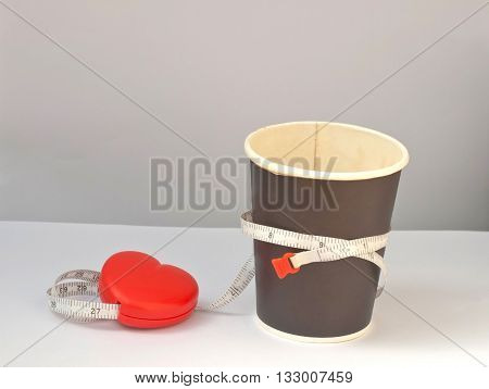 cup of coffee with measuring tape in diet concept