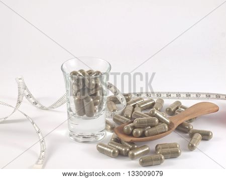 herb in capsule pill for diet on white background