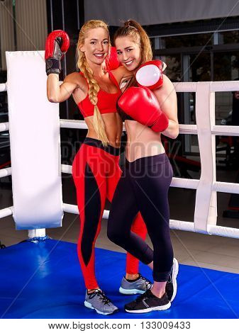 Two women boxer wearing red gloves posing in boxer ring.