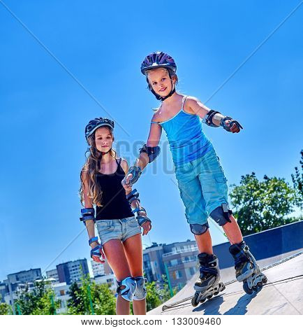 Sport children in helmet skateboarding on his skateboard outdoor. Childhood with skateboarding .