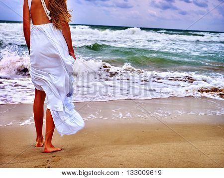 Summer girl sea. Woman goes at water on coast sea.