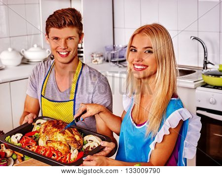 Happy family cooking chicken at kitchen. First cooking at home kitchen.