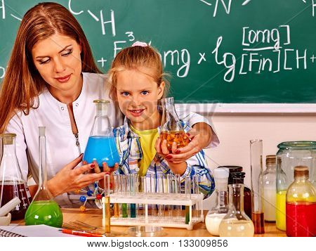 Child girl and chemistry teacher holding chemistry flask in chemistry class.