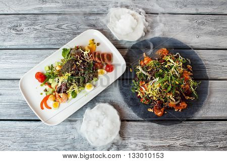 Salad plates on wooden background. Salads with shrimp and fish. Eggs and fresh arugula. Dishes served with dry ice.