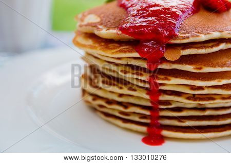 Pancakes with fresh strawberry and jem near glass with milk on white plate on white wooden background in garden or on nature background. Stack of pancakes on the table. Closeup.