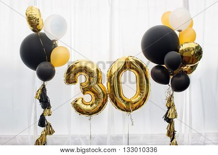 Decoration for birthday, anniversary, celebration of the thirtieth anniversary, white background, gold and black balloons with tassels