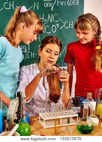 Children girl and teacher holding flask in chemistry class. Chemistry teacher in chemistry class learning children.