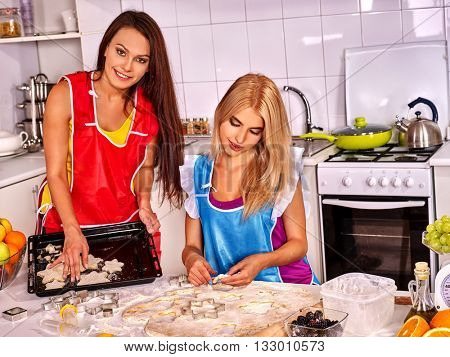 Two women friend kneading dough at table in kitchen. Cooking dough on home kitchen.